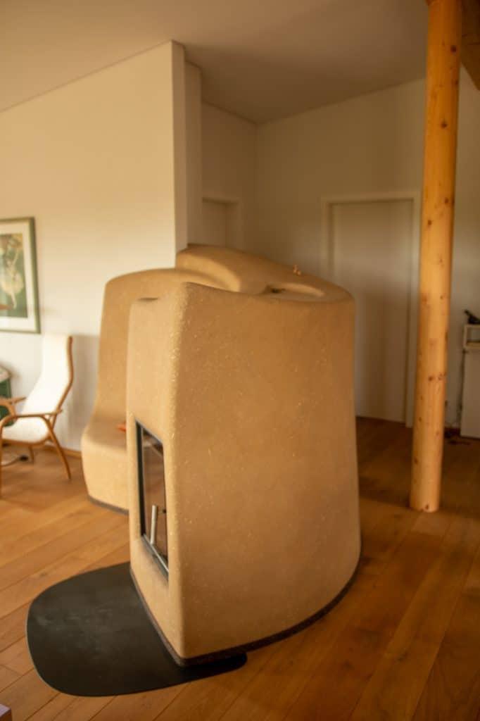 Zentraler Lehmofen im Wohnzimmer von der Seite