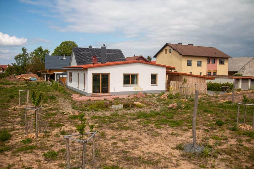 Blick Richtung Dorf auf das Einfamilienhaus mit angelegtem Garten und Teich
